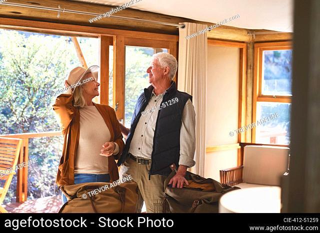 Happy playful senior couple in safari lodge hotel room