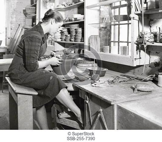 Young woman making pottery on a pottery wheel