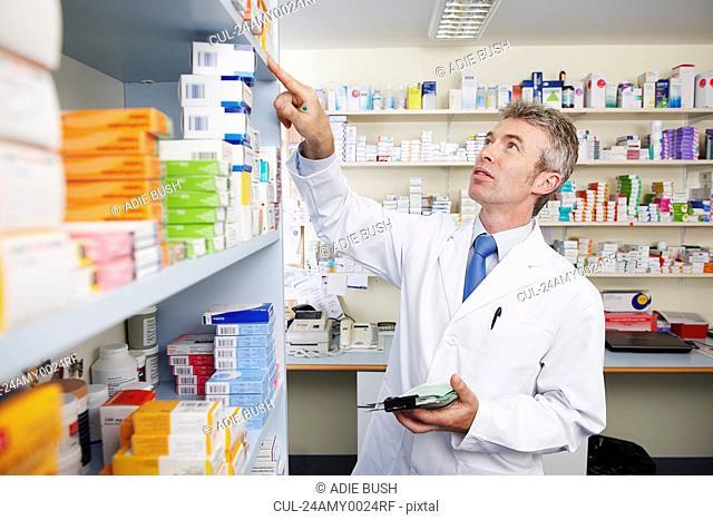 Pharmacist looking at shelf of pills