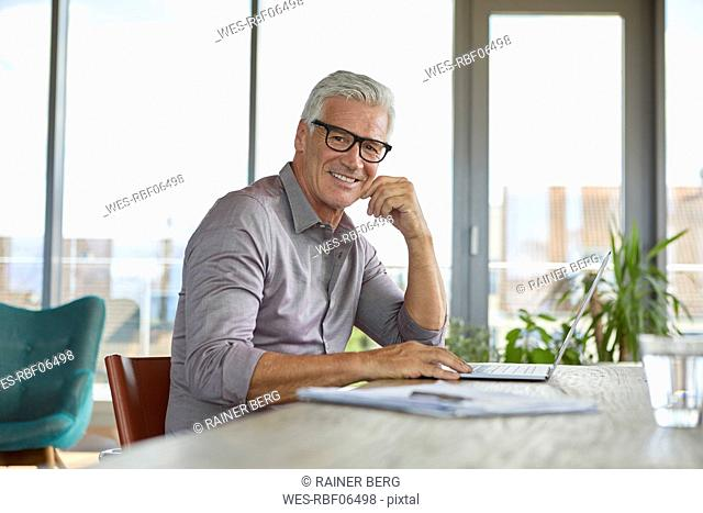 Portrait of smiling mature man using laptop on table at home