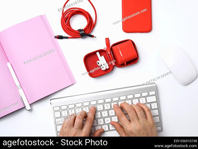 two female hands and a white keyboard, freelancer workplace with an open notebook, headphones, red smartphone, white table, top view