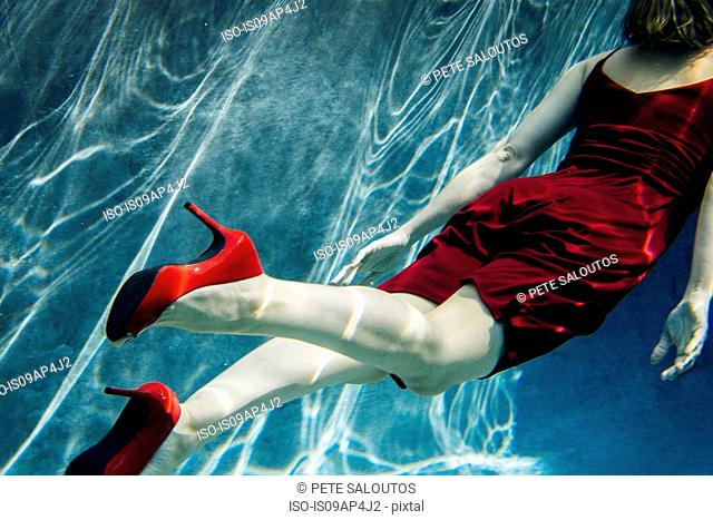 Mature woman wearing red dress and high heels, swimming, underwater view