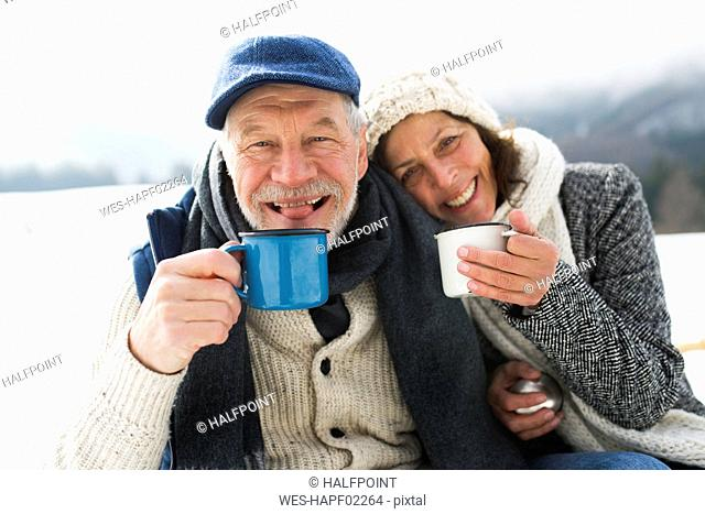 Portrait of senior couple with hot beverages in winter