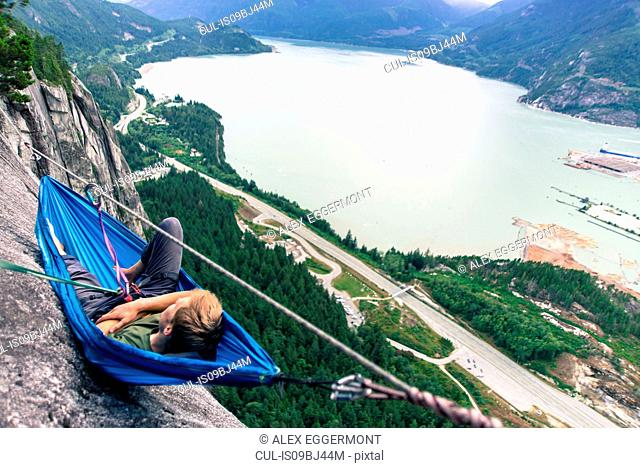 Young male climber reclining in hammock on bellygood ledge, The Chief, Squamish, Canada