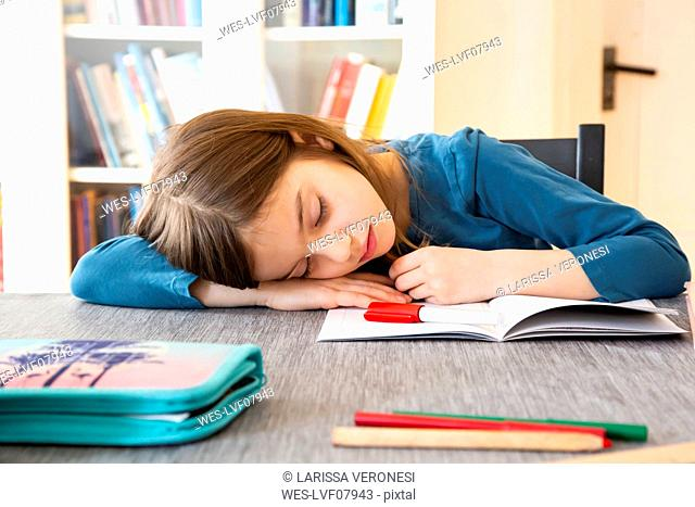 Schoolgirl napping at table with homework