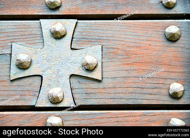 cross lombardy  arsago seprio abstract  rusty brass brown knocker in a door curch closed wood italy