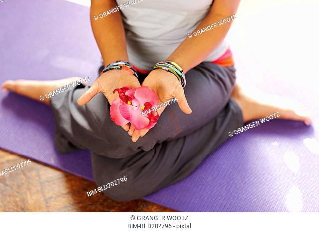 Mixed race woman with flowers on yoga mat