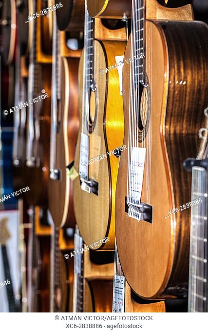 spanish guitars for sale hanging in a music shop
