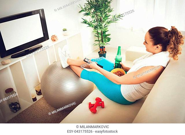 Lazy beautiful young woman in sport clothing sitting front of the TV and doesn't wont to exercise
