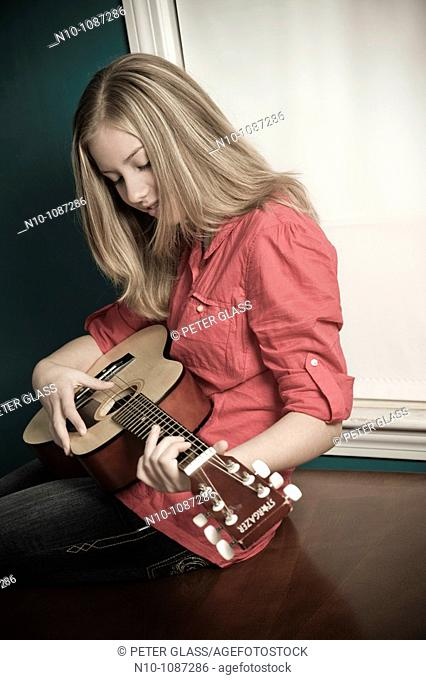 Blond preteen girl playing a guitar