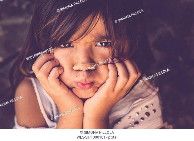 Portrait of girl pouting mouth with head in her hands