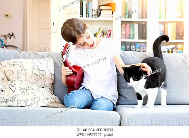 Girl with ukulele sitting on couch stroking cat