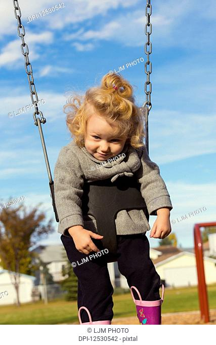 A cute young girl playing looking down with a funny face while swinging in a playground during the fall season; Spruce Grove, Alberta, Canada