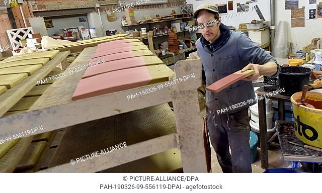 26 March 2019, Brandenburg, Glindow: Martin Grade glazes the roof tiles for a Belgian church in the brick factory. The company with 20 employees produces bricks...