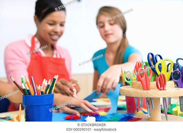Teacher and student in art class with supplies in foreground selective focus