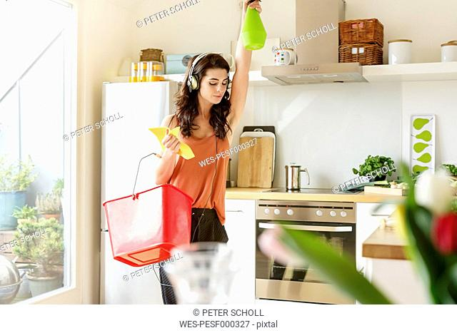Young woman in kitchen cleaning and listening to music