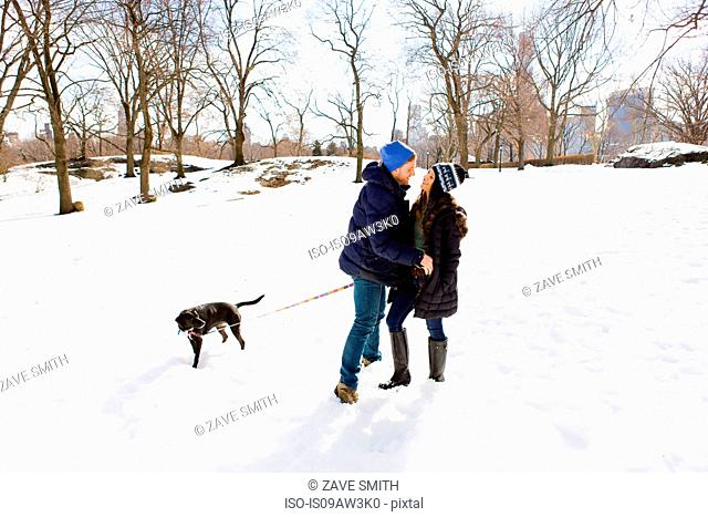 Romantic young couple standing together in snow with dog, Central Park, New York, USA