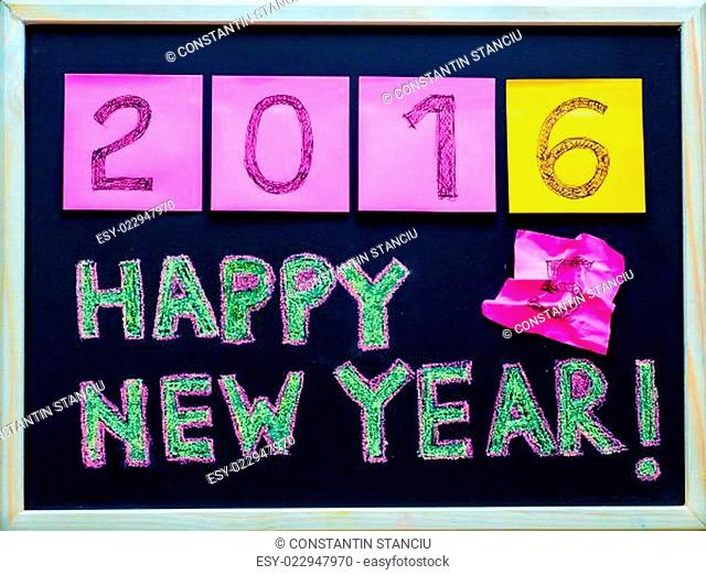 Happy New Year 2016 message hand written on blackboard, numbers stated on post-it notes, 2016 replacing 2015, corporate office celebration concept