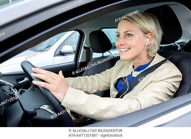 Female car driver is hearing music