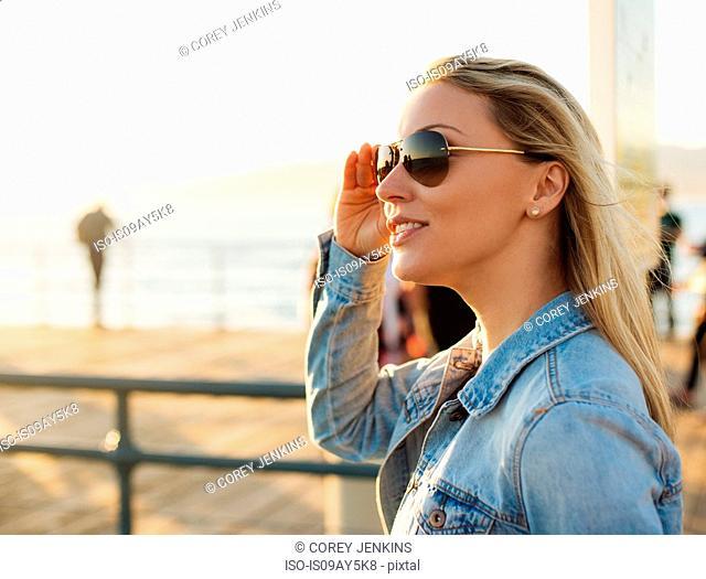Young blond woman on sunlit pier, Santa Monica, California, USA