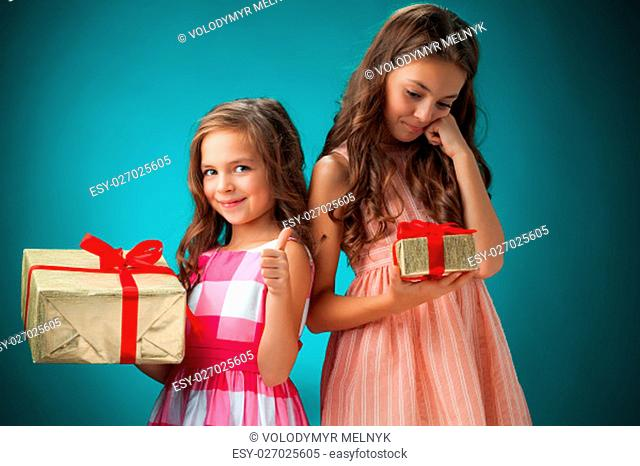 The two cute cheerful little girls with gift and festive cap on blue background