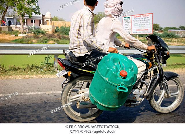 Two people riding along a highway in Uttar Pradesh, India