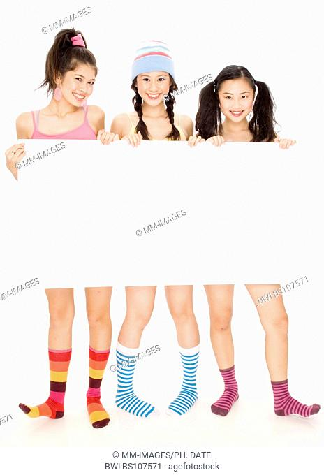 Three pretty young teenagers holding a blank sign