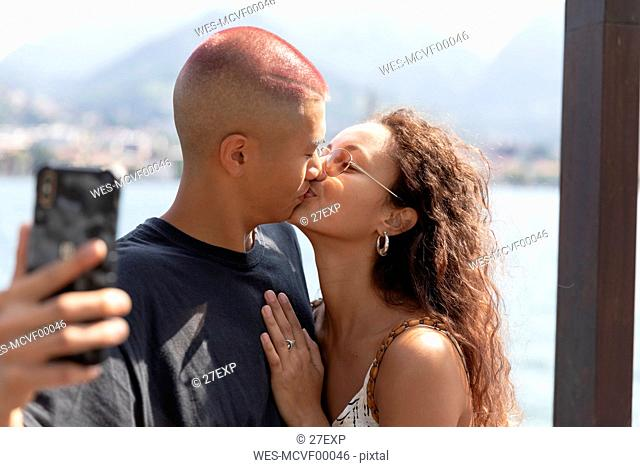 Young couple taking selfie with cell phone while kissing, Lecco, Italy