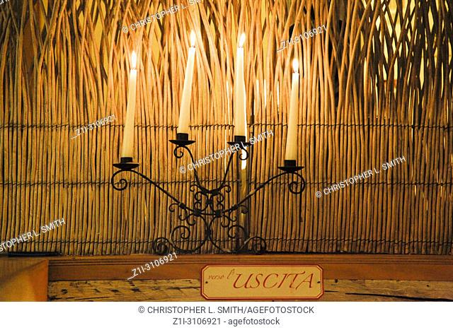 Candles enhance the atmosphere inside the Trattoria Antica Maddalena restaurant on Via Pelliccerie in Udine, Italy