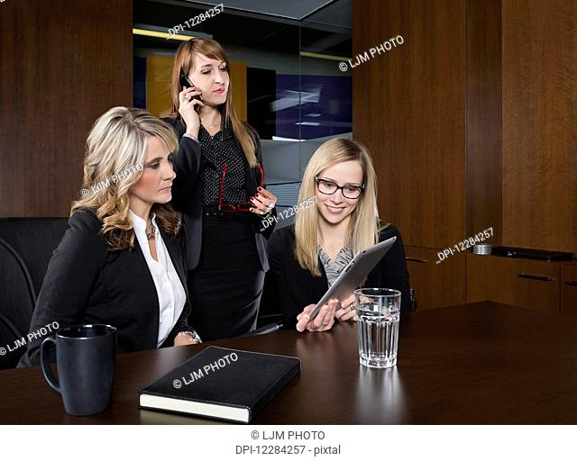 Three professional business women during a training session in a boardroom; St. Albert, Alberta, Canada