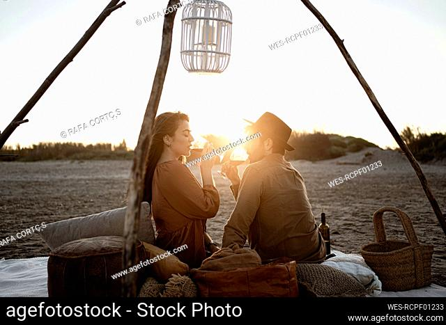 Couple drinking wine while sitting at beach during sunset