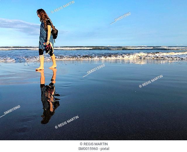 Young teenage girl walking alone on a beach