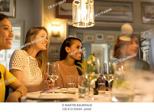 Smiling women friends looking away dining and drinking white wine at restaurant table