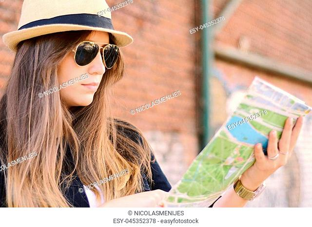Beautiful traveler woman looking at the map. Freedom and active lifestyle concept
