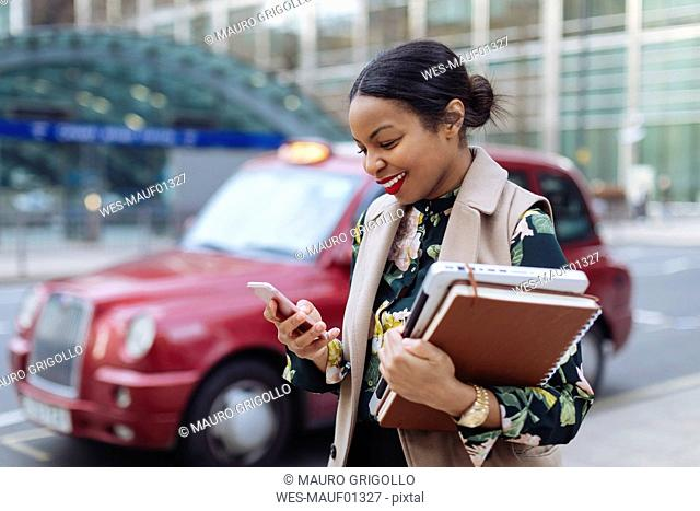 UK, London, happy businesswoman looking at cell phone
