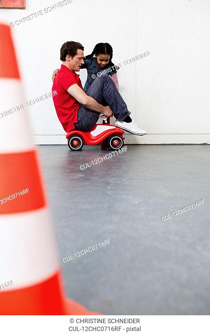 young girl teaching man to ride toy car