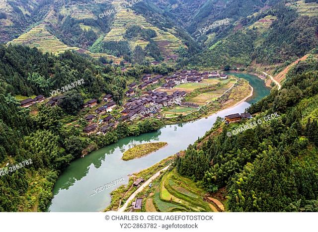 Guizhou, China. Terraced Rice Cultivation on Hillsides above Small Village and Stream between Zhaoxing and Kaili
