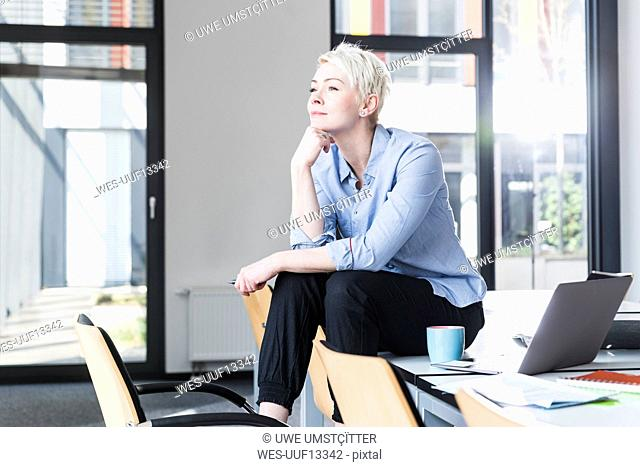 Smiling woman sitting on table in office