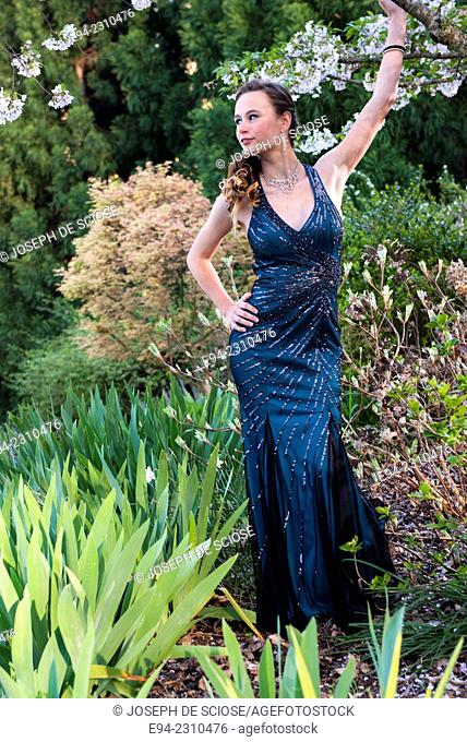 An 18 year old woman in a formal dress looking from the camera in garden setting