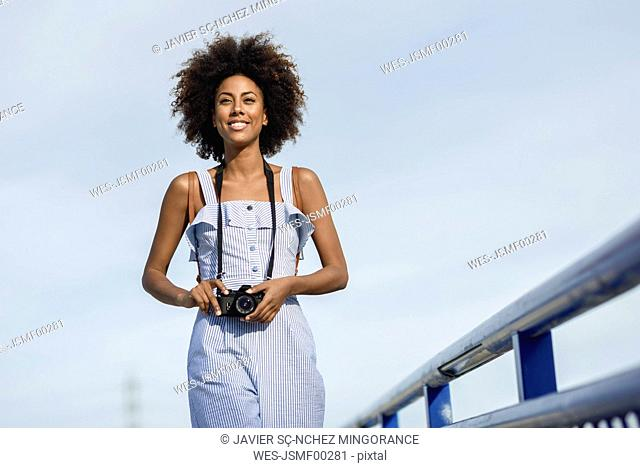 Portrait of smiling young woman with camera against sky