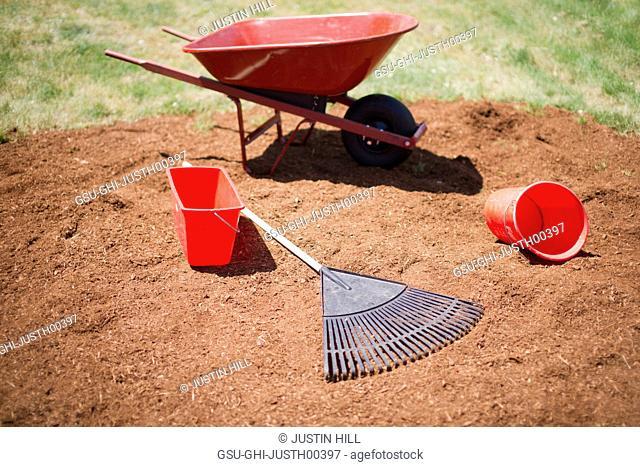 Wheelbarrow, Buckets and Rake on Pile of Mulch