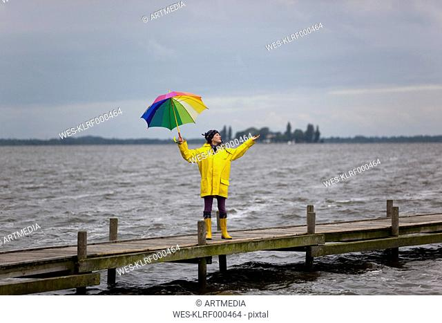 Germany, Steinhuder Meer, woman wearing yellow rain coat and Wellington boots standing on jetty