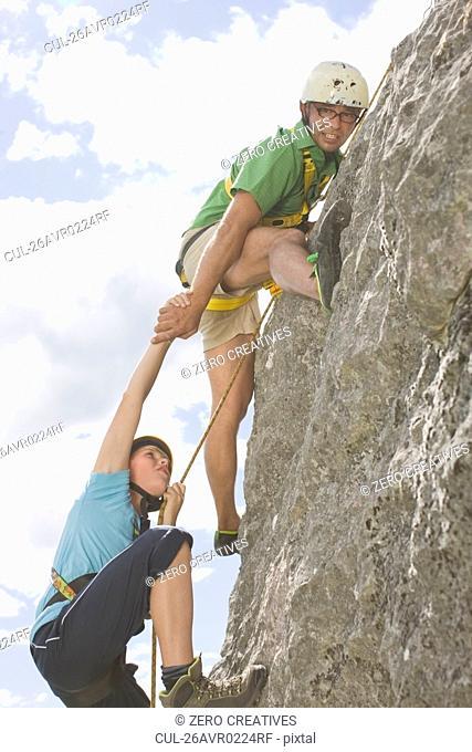 Boys climbing a rock