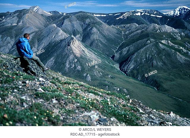 Hiker on a hilltop view into the valley of Noatak River Brooks Range Alaska USA