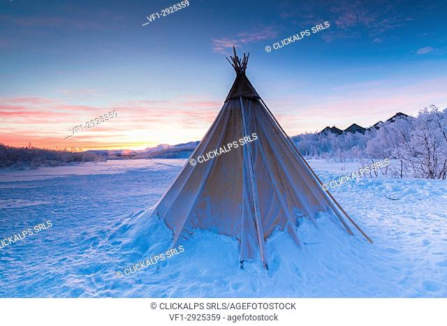 Pink sky at sunrise on isolated Sami tent in the snow, Abisko, Kiruna Municipality, Norrbotten County, Lapland, Sweden