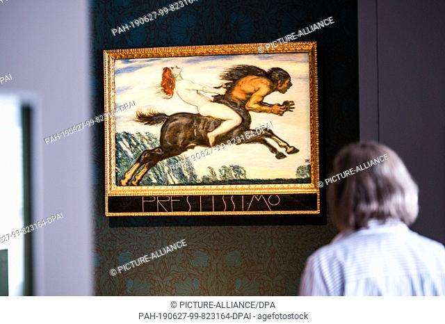 """27 June 2019, Hessen, Wiesbaden: A visitor looks at Franz von Stuck's artwork """"""""Prestissimo"""""""" in the exhibition. The Hessisches Landesmuseum für Kunst und Natur..."""