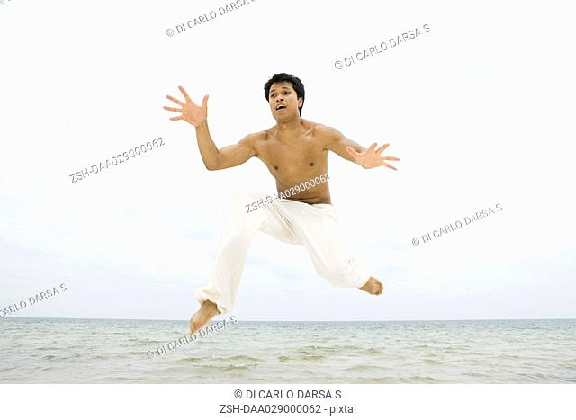 Man jumping in the air at the beach