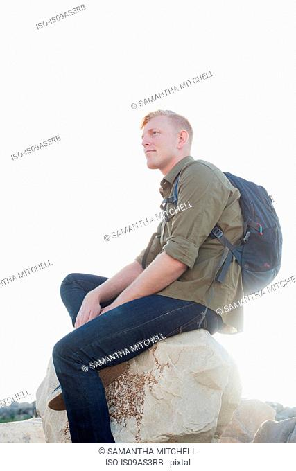 Young man wearing backpack sitting on rock looking away