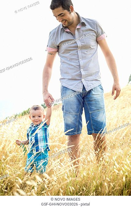 Smiling Man and Young Boy Walking Through Field