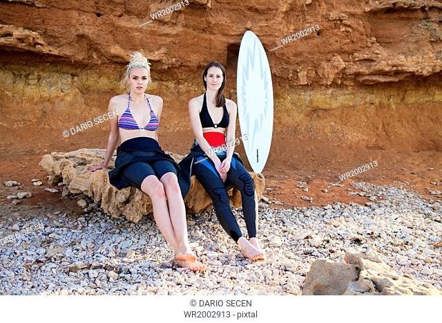 Female surfers in front of rock